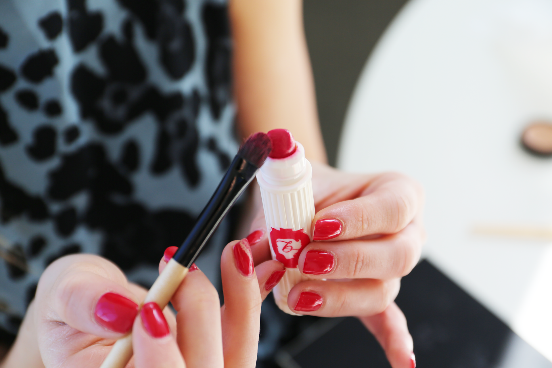 A smaller make-up brush is used to apply the lipstick outline