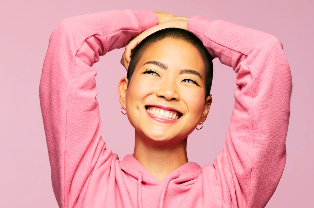 Model wearing a pink shirt smiling